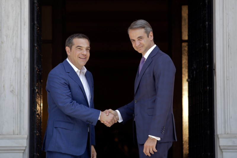 Greece's newly-elected prime minister Kyriakos Mitsotakis shakes hands with outgoing prime minister Alexis Tsipras, as Tsipras leaves the Maximos Mansion on July 8 in Athens.