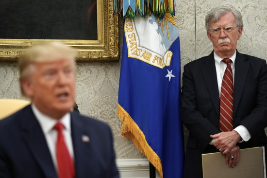 White House National Security Advisor John Bolton listens to U.S. President Donald Trump as he and Dutch Prime Minister Mark Rutte talk to reporters in the Oval Office at the White House on July 18.