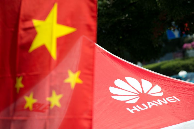 The logo of Huawei is seen next to a Chinese flag in Shanghai on Oct. 1, 2014.
