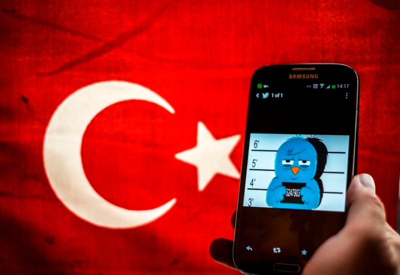 A picture representing a mug shot of the Twitter bird is seen on a smartphone in front of a Turkish flag in Istanbul on March 26, 2014.
