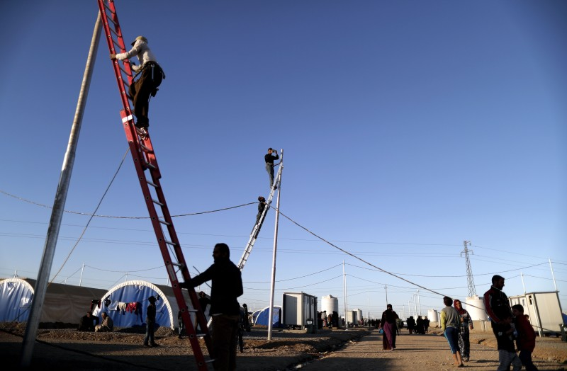 Workers install electric wires at the Khazir refugee camp west of Erbil on Nov. 21, 2016.
