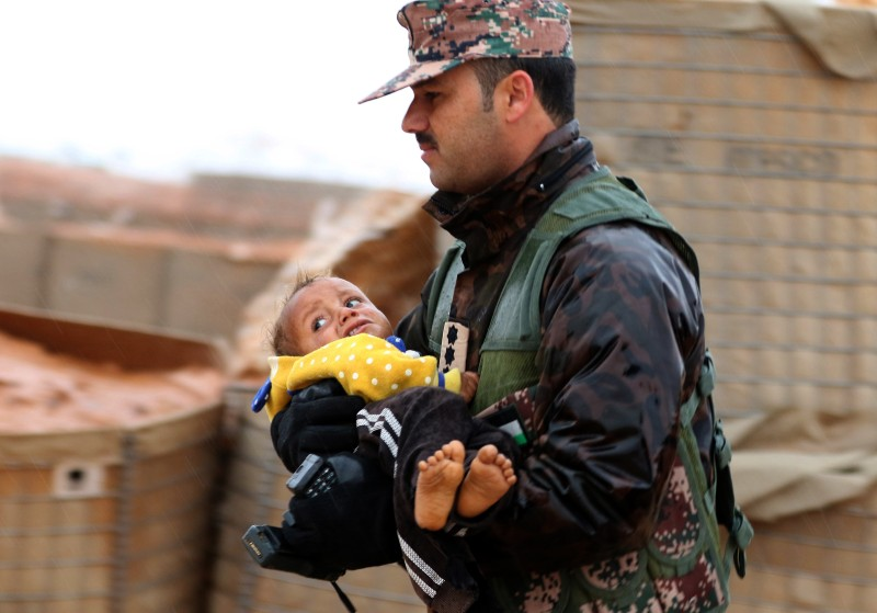 A member of the Jordanian armed forces carries a toddler from the informal Rukban camp, which lies in no-man's-land off the border between Syria and Jordan, outside a U.N.-operated medical clinic immediately on the Jordanian side on March 1, 2017.