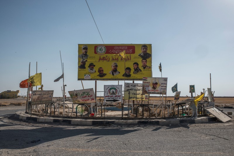 Iraqi Shiite militia banners are seen by a road in the Iraqi town of Baaj near the Iraq-Syria border on June 20, 2017.