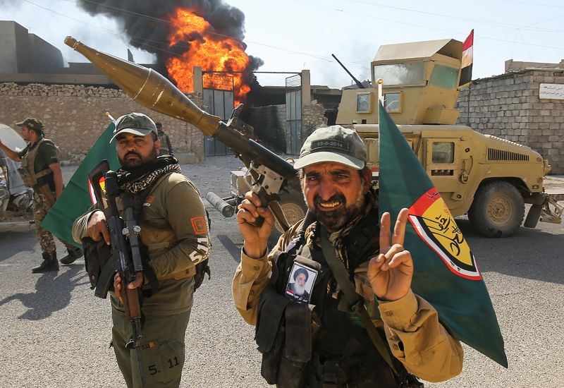 Popular Mobilization Unit fighters flash the victory gesture as they advance through a street in the town of Tal Afar, west of Mosul, on Aug. 26, 2017.