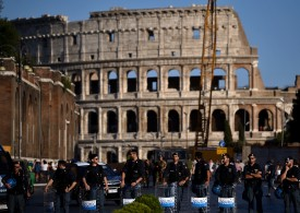 Police stand guard on the street in front of the Colosseum near concrete blocks placed to prevent vehicle attacks in central Rome on Aug. 26, 2017.
