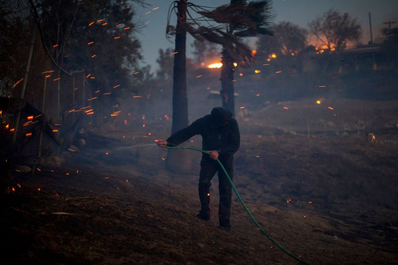 A strong wind blows embers around a resident hosing his burning property during the Creek Fire in Sunland, California, on Dec. 5, 2017.