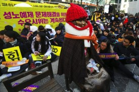 "Protestors sit next to a statue symbolizing former ""comfort women,"" who were forced into sexual slavery by Japan during World War II, during a weekly rally near the Japanese Embassy in Seoul on Jan. 10, 2018."