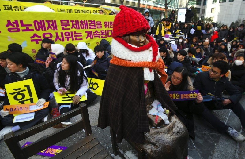"""Protestors sit next to a statue symbolizing former """"comfort women,"""" who were forced into sexual slavery by Japan during World War II, during a weekly rally near the Japanese Embassy in Seoul on Jan. 10, 2018."""