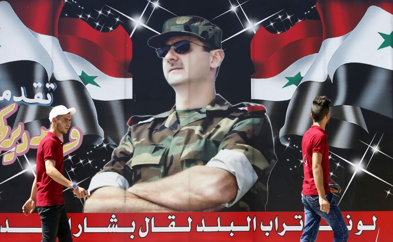 "Syrian youths walk past a billboard showing a picture of Syrian President Bashar al-Assad wearing sunglasses while dressed in a Field Marshal's camouflage fatigues, on display in the centre of the capital Damascus on July 9, 2018, with a caption below reading in Arabic: ""If the country's dust speaks, it will say Bashar al-Assad."""