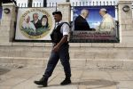 A Palestinian policeman stands guard near a banner bearing portrait of Pope Francis and Palestinian Authority President Mahmud Abbas displayed in the Church of Nativity, in the West Bank city of Bethlehem, on May 19, 2014.