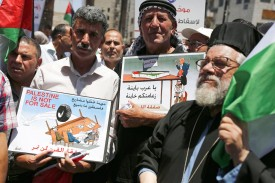Palestinian demonstrators carry caricatures during a protest against the  U.S.-led peace plan in Ramallah on June 24.
