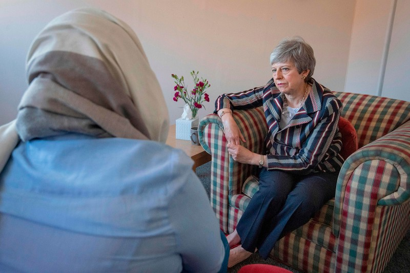 Britain's then-Prime Minister Theresa May talks with a survivor of domestic violence on a visit to a charity providing support for victims in west London on May 13, before she stepped down.