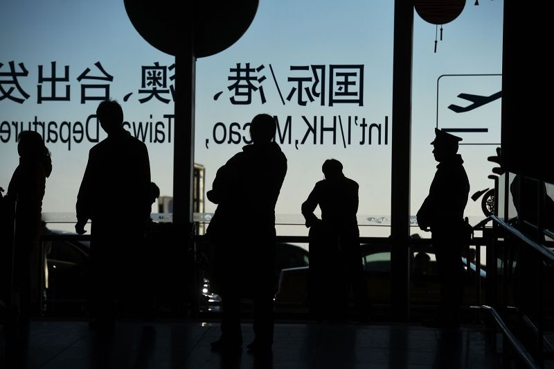 Travelers stand near the international departures area at the airport in Beijing on Feb. 6, 2016.
