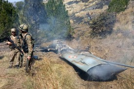 Pakistani soldiers stand next to what Pakistan says is the wreckage of an Indian fighter jet shot down in Pakistan-controlled Kashmir near the Line of Control on Feb. 27.