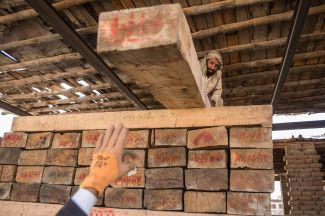 Day laborers stack planks of wood that arrived from Kunar at a storage facility in Jalalabad, Afghanistan, on May 30.