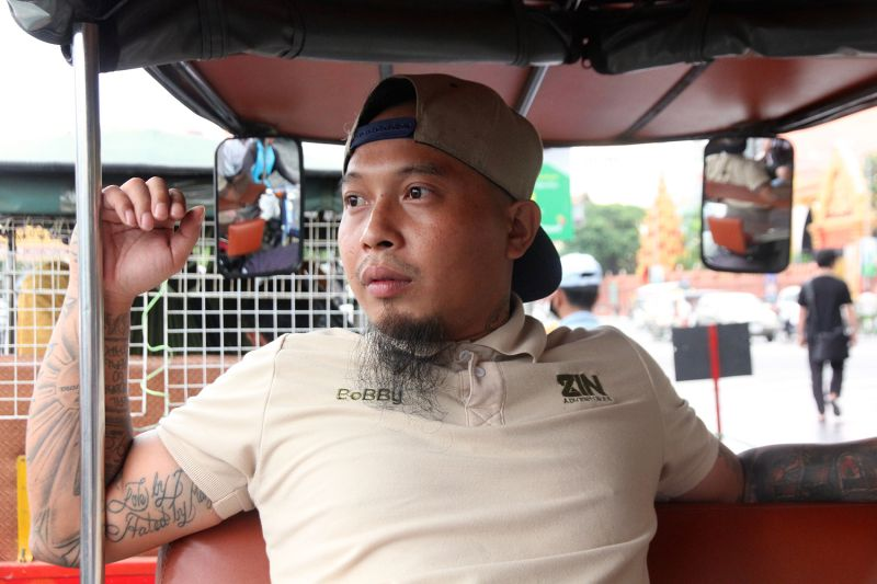 Buck Billy is a co-owner of ZIN Adventures, a tour company owned and operated by deportees. He rides in a tuk tuk during ZIN's Good Luck City Tour in Phnom Penh on June 5.