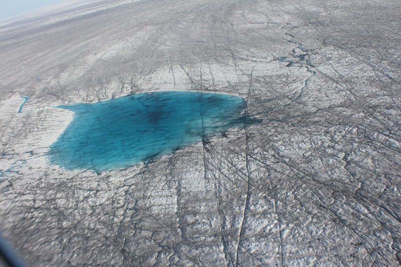 A Greenland ice melt lake atop the sheet, seen from 5,000 feet above, in August. Across Greenland's massive ice sheet, blue pools of melted water, forming icy lakes, dot the landscape as far as the eye can see.