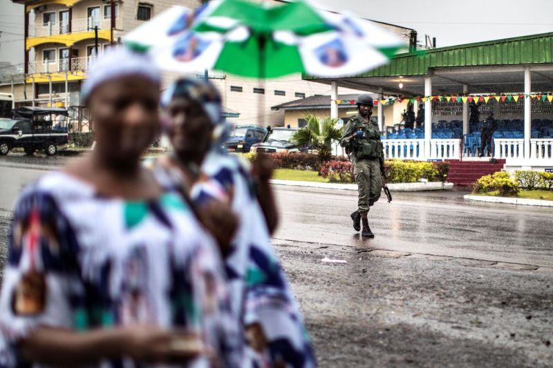 Supporters of Cameroonian President Paul Biya's party, the Cameroon People's Democratic Movement, walk through Bongo Square under the watch of a gendarme in Buea, Cameroon, on Oct. 3, 2018.