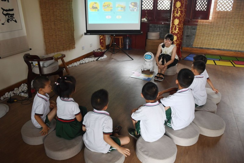 An educator introduces a Keeko robot to children at the Yiswind Institute of Multicultural Education in Beijing on July 30, 2018.