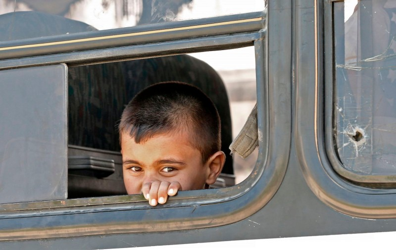 A young Syrian refugee peeks out of a bus window as fellow refugees prepare to leave Beirut on their journey home to Syria on Sept. 4, 2018.