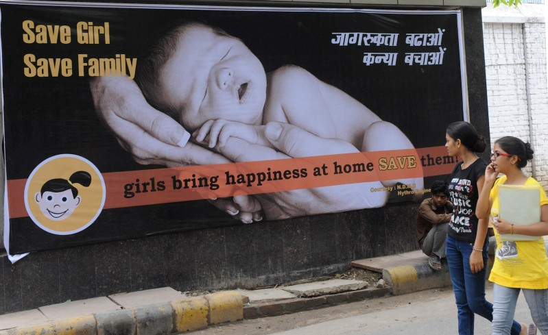 Young Indian women walk past a billboard in New Delhi encouraging the birth of girls on July 9, 2010.