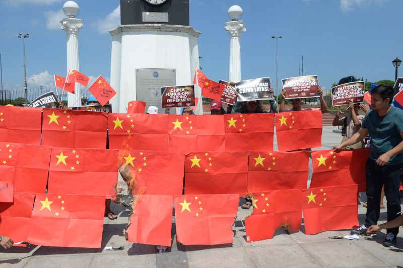 Activists burn Chinese flags and display anti-China placards during a protest at a park in Manila on June 18, 2019.