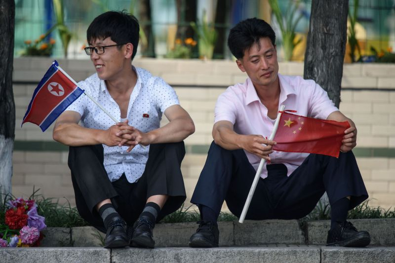 Two men sit holding North Korean and Chinese flags near Kim Il Sung Square in Pyongyang on June 20, as Chinese President Xi Jinping visits the country.