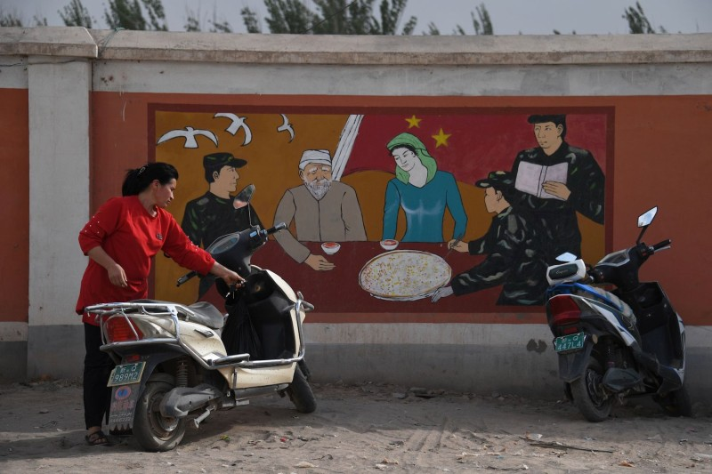 A Uighur woman stands beside a propaganda painting showing soldiers meeting with a Uighur family, outside a military hospital near Kashgar in China's northwest Xinjiang region on July 2, 2019.