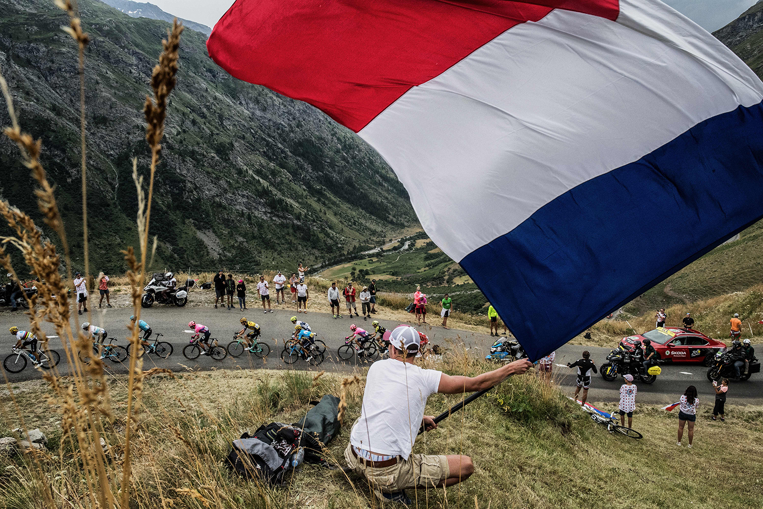 A fan waves a French national flag as the pack rides uphill during the 19th stage of the Tour de France cycling race between Saint-Jean-de-Maurienne and Tignes on July 26. JEFF PACHOUD/AFP/Getty Images