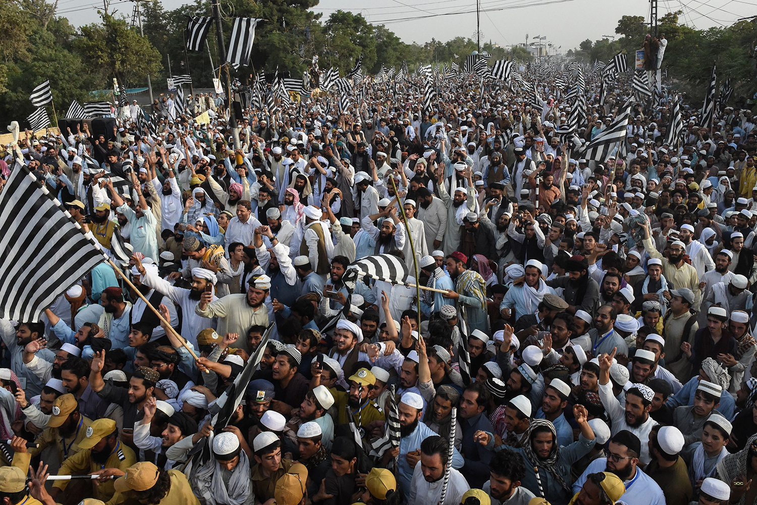 Supporters of the Jamiat Ulma-e-Islam political party wave flags during an anti-government rally in Quetta, Pakistan, on July 28. The prime minister faces growing anger by opposition parties which accuse his government of being responsible for the teetering economy, running inflation, and unemployment in the country. BANARAS KHAN/AFP/Getty Images