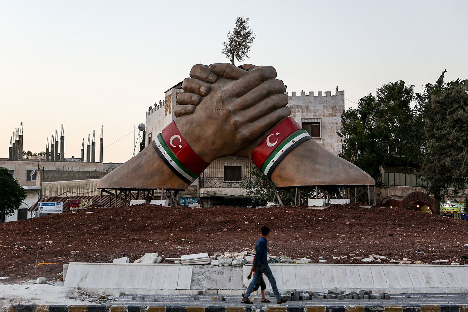 A giant sculpture features crossed hands with bracelets showing the Turkish and Syrian Rebel flags stands in a roundabout in the town of Azaz in the heart of a Turkish zone of influence in Syria's northern Aleppo province north of Aleppo near the Turkish border on July 27. NAZEER AL-KHATIB/AFP/Getty Images