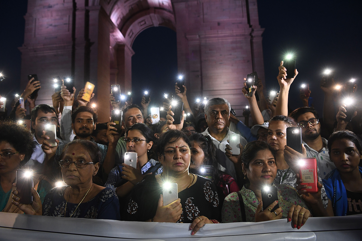 Indian social activists take part in a rally in front of the India Gate monument in solidarity with the Unnao rape victim in New Delhi on July 29. An Indian teenager who accused a senior politician of rape is fighting for her life after being critically injured in a crash that killed two relatives, raising suspicions of foul play. SAJJAD HUSSAIN/AFP/Getty Images
