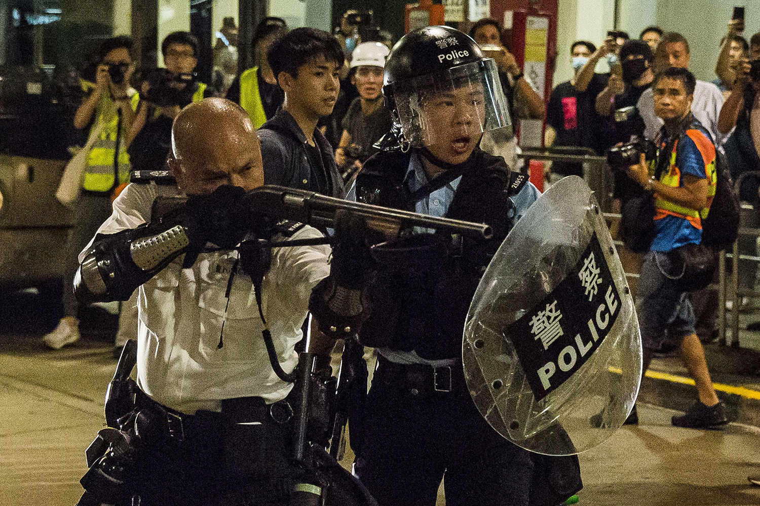 A police officer points a firearm during a clash with protesters who had gathered outside Kwai Chung police station, in support of protesters detained and charged with rioting, in Hong Kong on July 30. ISAAC LAWRENCE/AFP/Getty Images