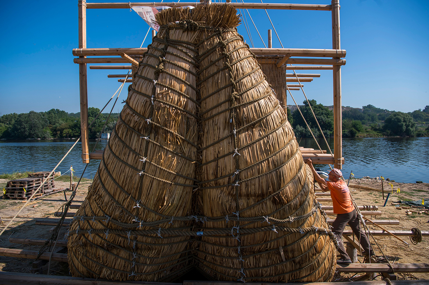A member of the crew assembles a sailing reed boat Beloslav, Bulgaria, on July 25. A team of researchers and volunteers from eight countries are preparing to set out on a 7000-nautical-mile voyage to test the hypothesis that prehistoric trade routes traversed the high seas. NIKOLAY DOYCHINOV/AFP/Getty Images