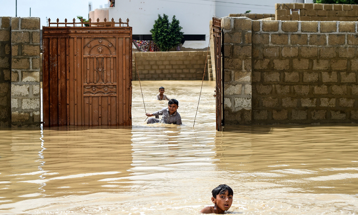 Young boys play among floodwaters during heavy monsoon rains in Karachi, Pakistan, on July 31. RIZWAN TABASSUM/AFP/Getty Images