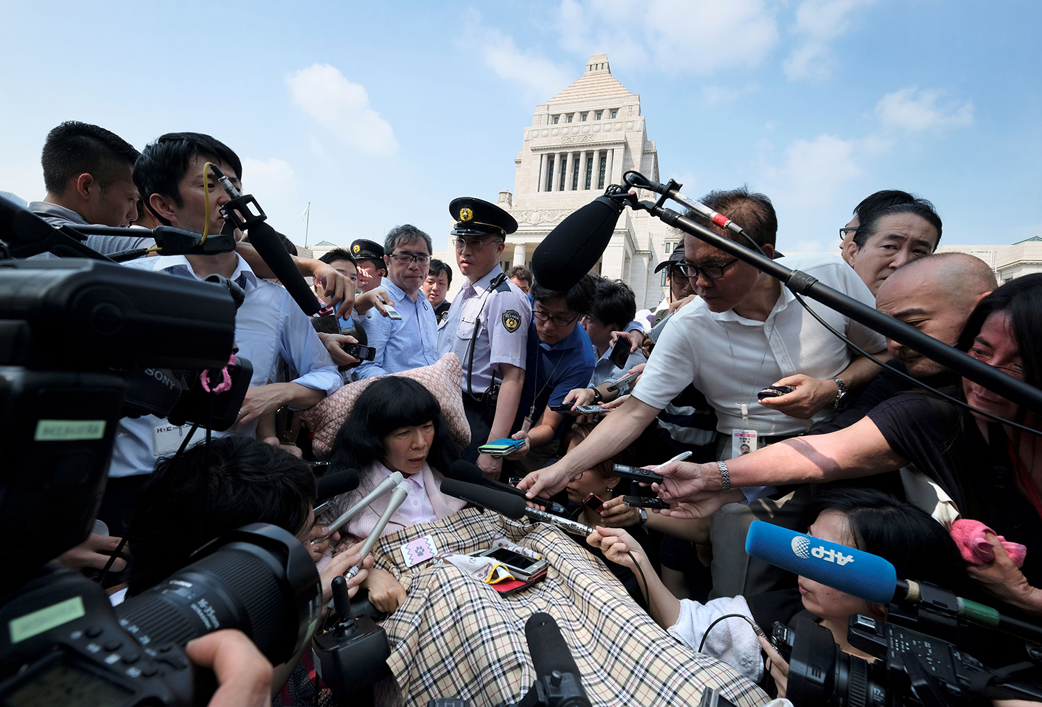 Japanese lawmaker Eiko Kimura is surrounded by the media upon her arrival at Parliament in Tokyo on Aug. 1. Two lawmakers with serious paralysis took their seats in Japan's upper house to cheers from supporters, marking the first time those with severe disabilities have served in the body. KAZUHIRO NOGI/AFP/Getty Images