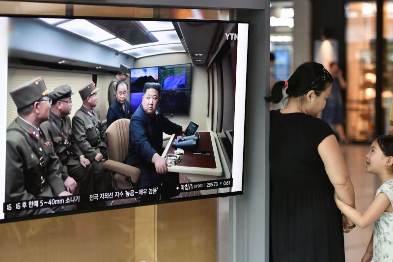 A woman and a girl chat next to a television news screen showing an image of North Korean leader Kim Jong Un looking at the test-fire of a new multiple rocket launcher, at a railway station in Seoul on Aug. 1.