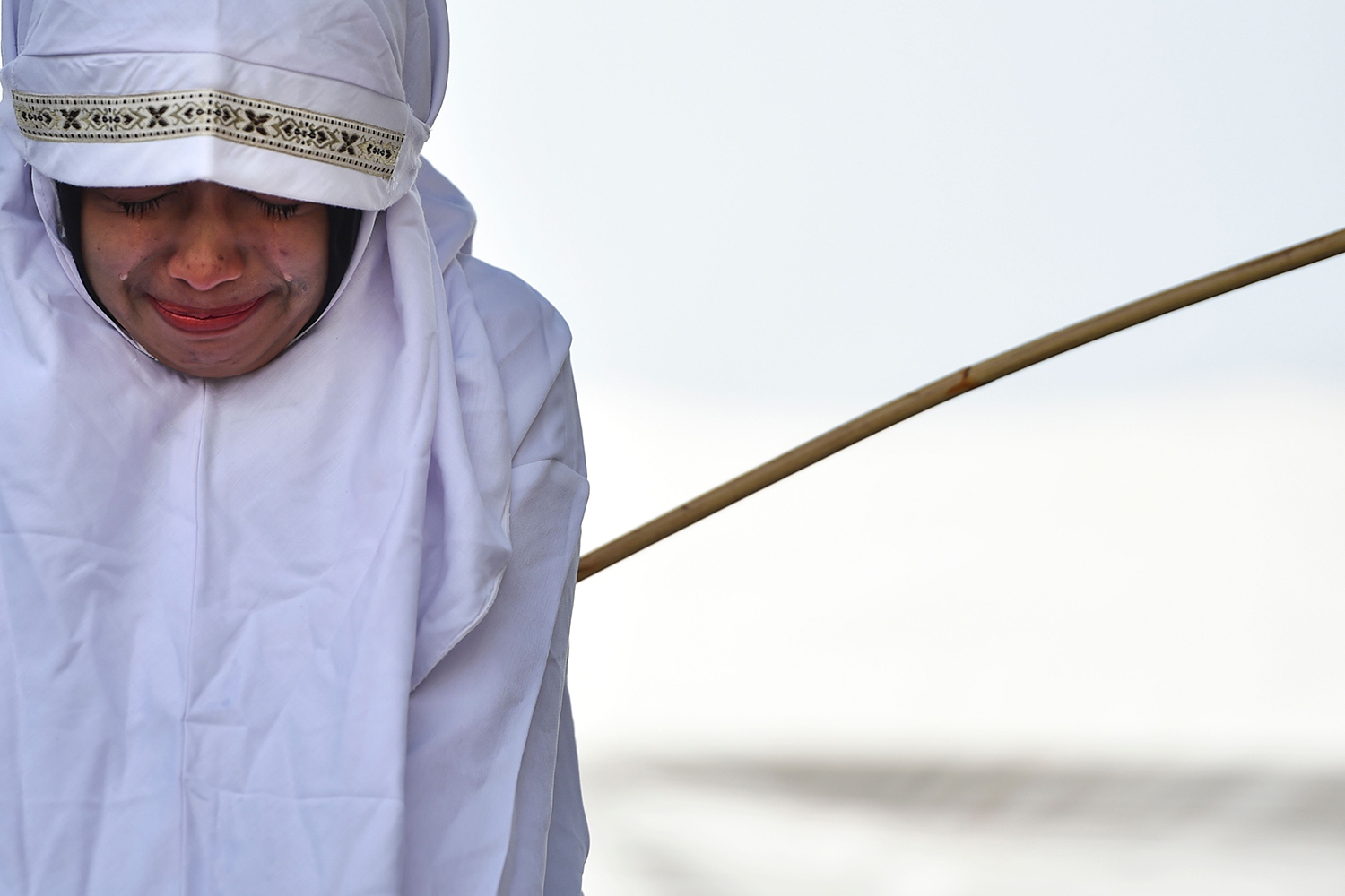 A woman is whipped in public in Banda Aceh in Indonesia's conservative Aceh province as punishment for being too close to the opposite sex on Aug. 1. Six men and five women, all in their late teens and early 20s, received between eight and 32 strokes as dozens of spectators watched. CHAIDEER MAHYUDDIN/AFP/Getty Images