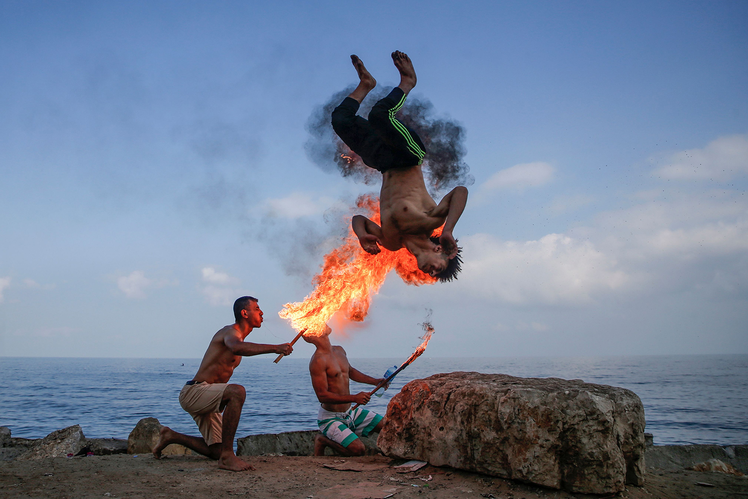 Palestinian men perform fire breathing on the beach as an entertainment for children during the summer vacation in Gaza City on Aug. 1. MOHAMMED ABED/AFP/Getty Images