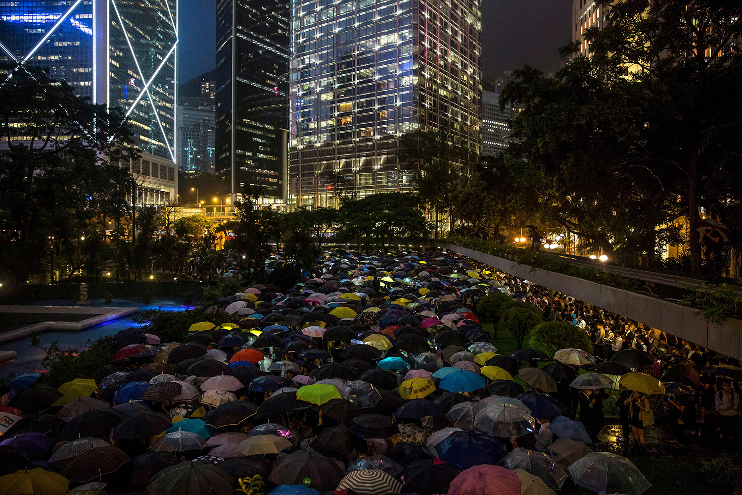 People from the finance community hold umbrellas and shine lights during a protest against a controversial extradition bill in Hong Kong on Aug. 1. ISAAC LAWRENCE/AFP/Getty Images