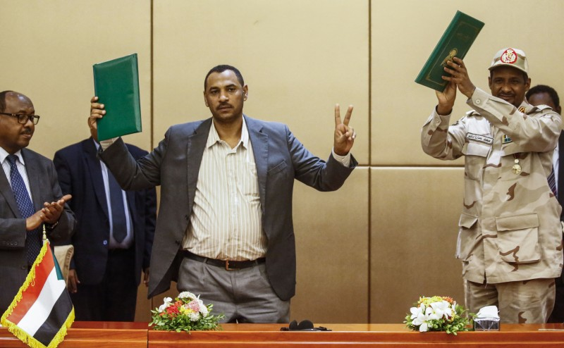 From left, Ethiopian mediator Mahmoud Drir, protest leader Ahmed al-Rabie, and Gen. Mohamed Hamdan Dagalo, Sudan's deputy head of the Transitional Military Council, celebrate after signing the constitutional declaration in Khartoum on Aug. 4.