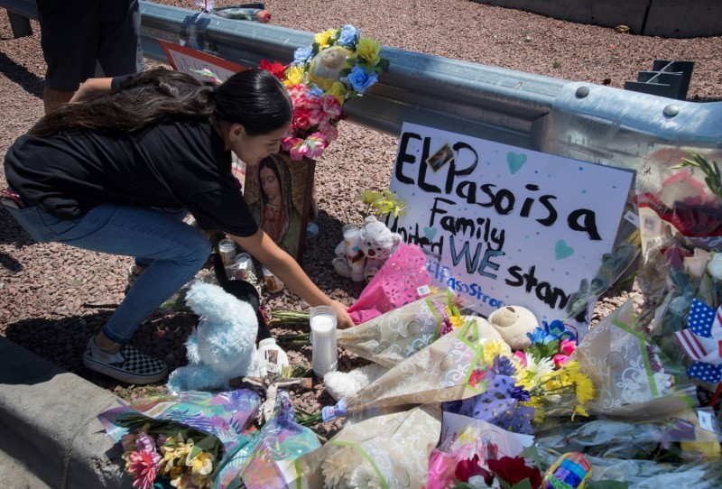 A woman places flowers beside a makeshift memorial outside the Cielo Vista Mall Wal-Mart where a shooting left 20 people dead in El Paso, Texas, on August 4, 2019.