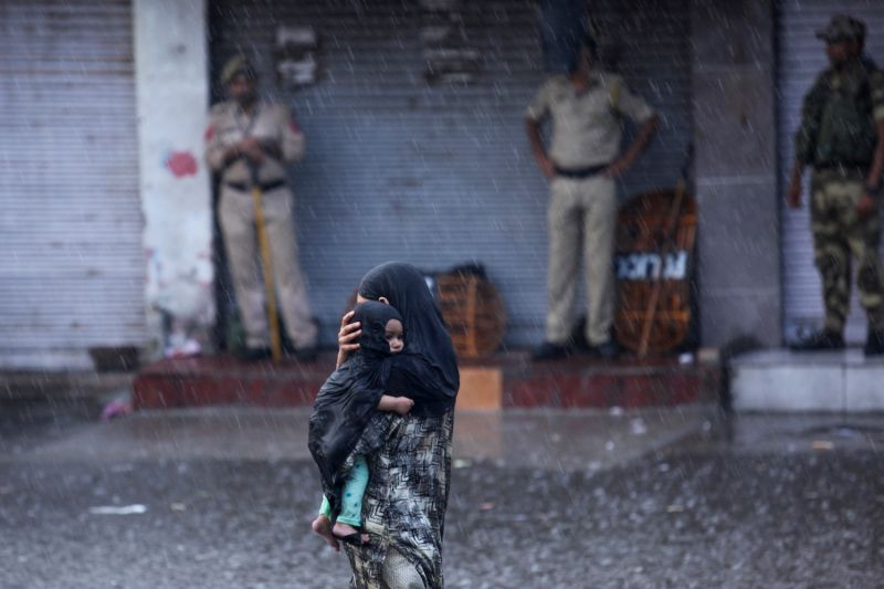 A woman holds her child as she walks past security personnel under rain in Jammu on Aug. 5.