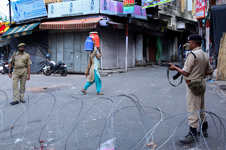 Security personnel stand guard on a street in Jammu on August 6.