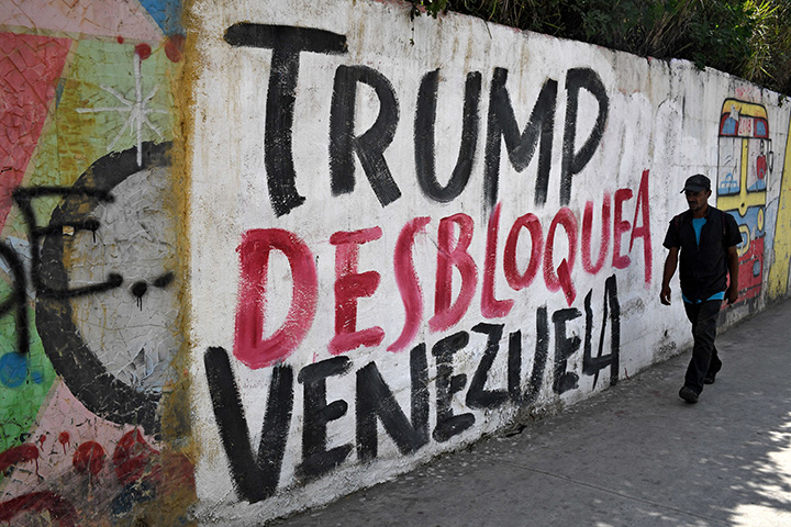 "A man walks past a wall reading ""Trump unblock Venezuela"" in Caracas on August 6."