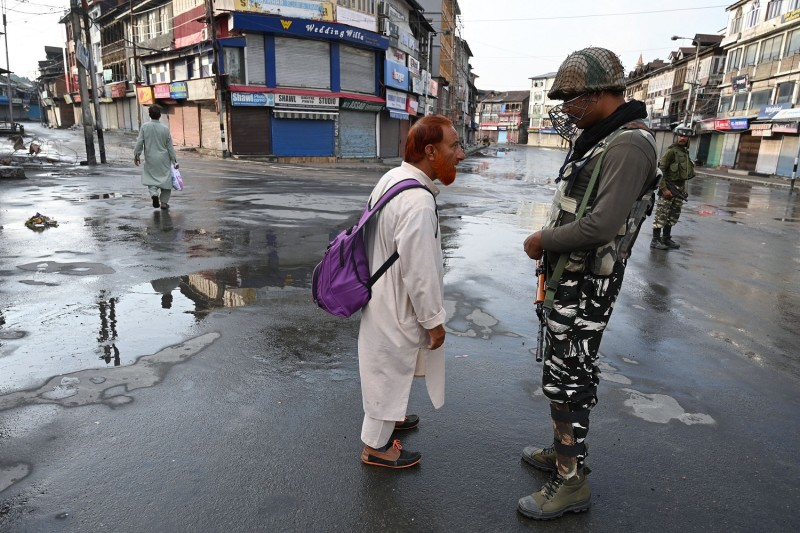 An Indian soldier questions a man on a street during a curfew in Srinagar on August 8, 2019.