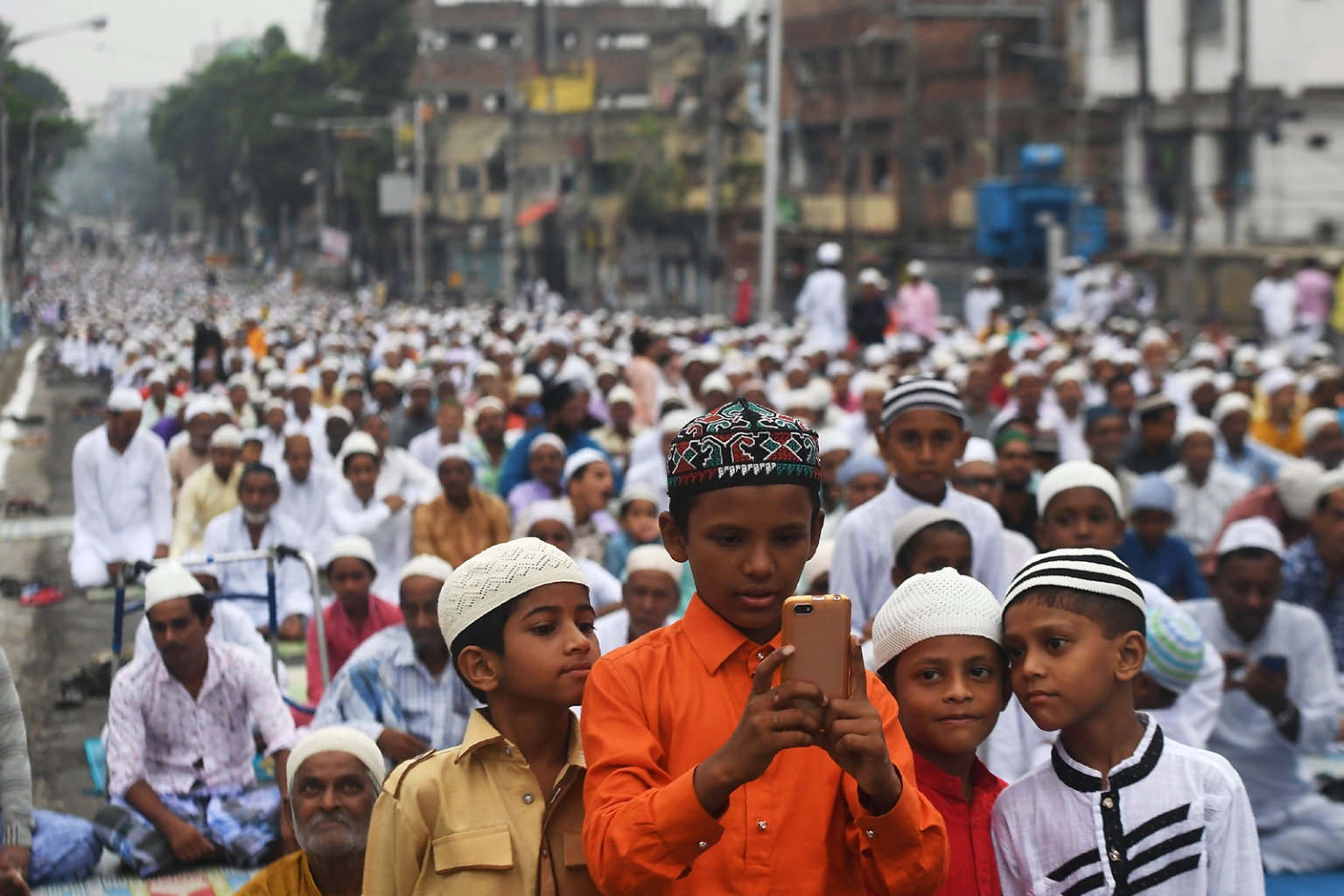 Young Muslims gather around a phone after participating in a special prayer organized to celebrate Eid al-Adha in Kolkata on Aug. 12. Muslims around the world celebrate the feast of sacrifice, the second of two Islamic holidays that mark the end of the annual hajj to Mecca. DIBYANGSHU SARKAR/AFP/Getty Images