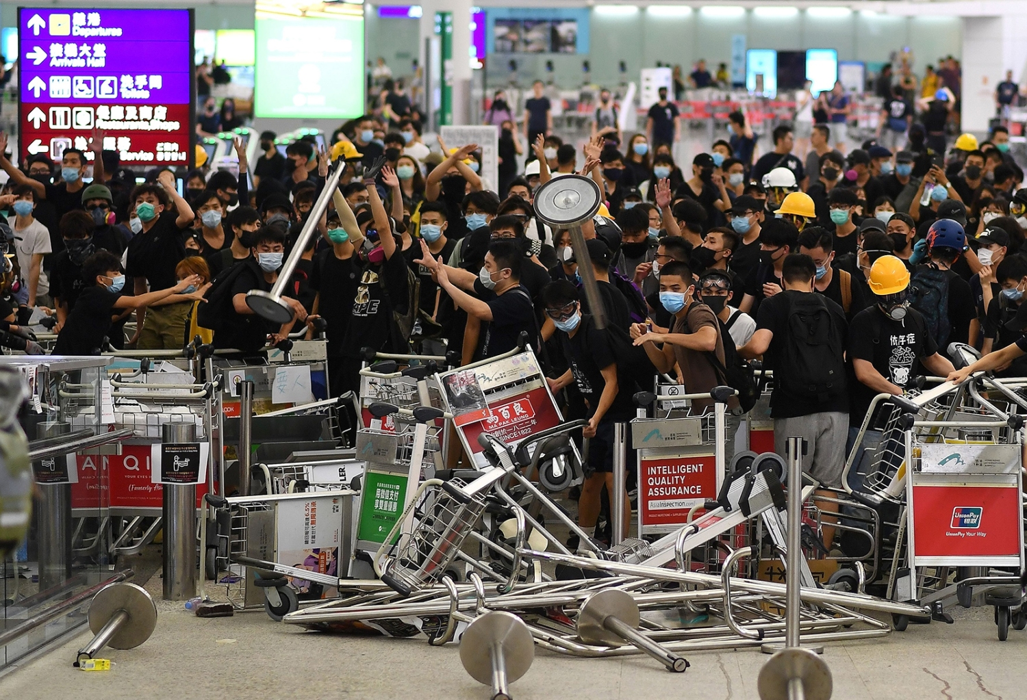 Pro-democracy protesters block the entrance to terminals after a confrontation with police at Hong Kong's International Airport on Aug. 13. MANAN VATSYAYANA/AFP/Getty Images
