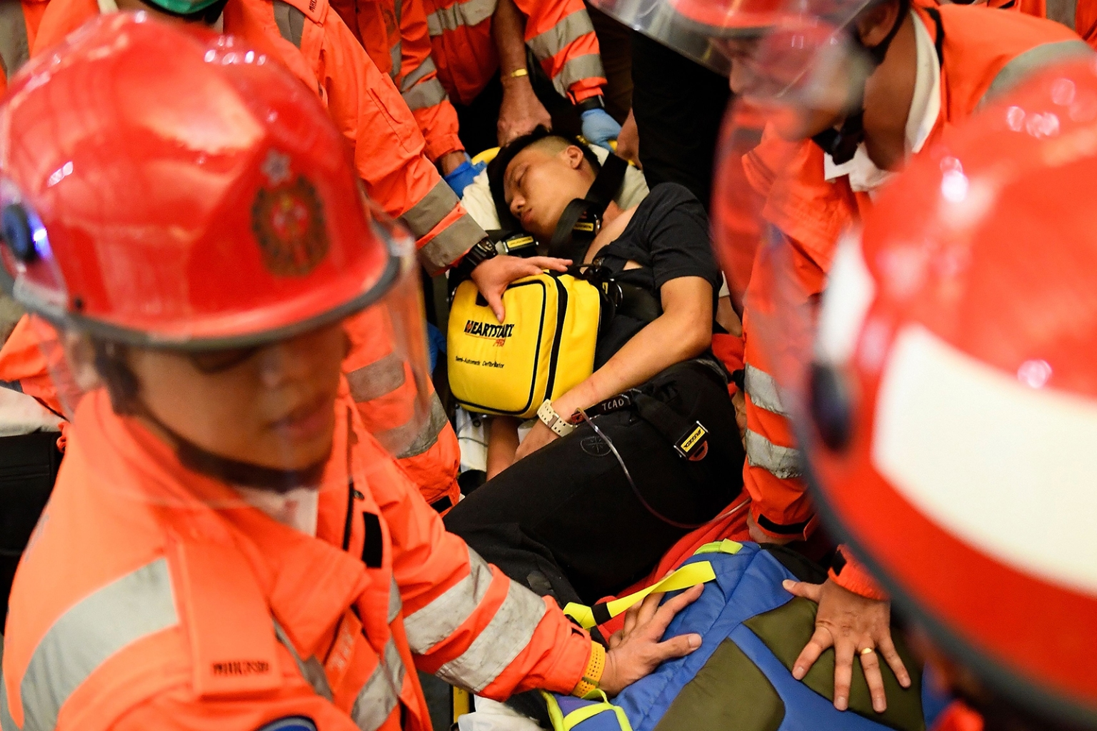 An injured man, suspected by protestors of being an undercover police officer, is taken away by paramedics at Hong Kong's International Airport, on Aug. 13. MANAN VATSYAYANA/AFP/Getty Images
