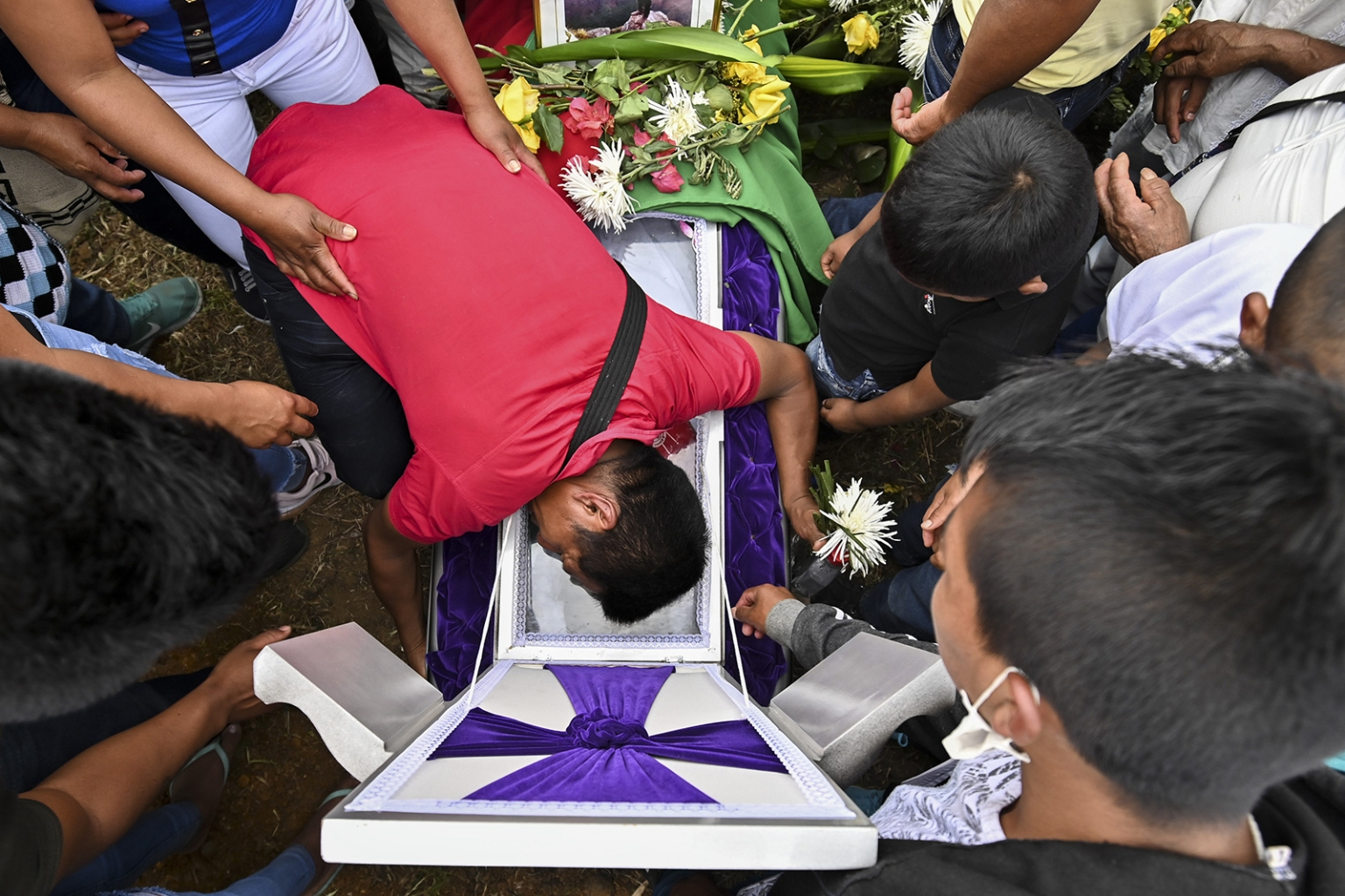 A relative mourns over the coffin of Kevin Mestizo—one of two members of the Nasa ethnic group Indigenous Guard killed by unknown assailants during an attack last weekend—during his funeral in Toribio, Colombia, on Aug. 13. LUIS ROBAYO/AFP/Getty Images